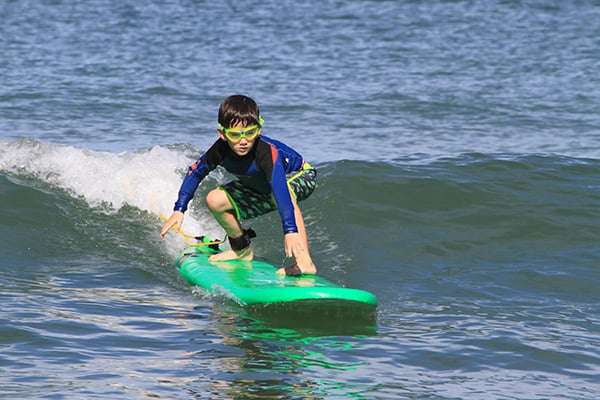 Little boy learning to surf