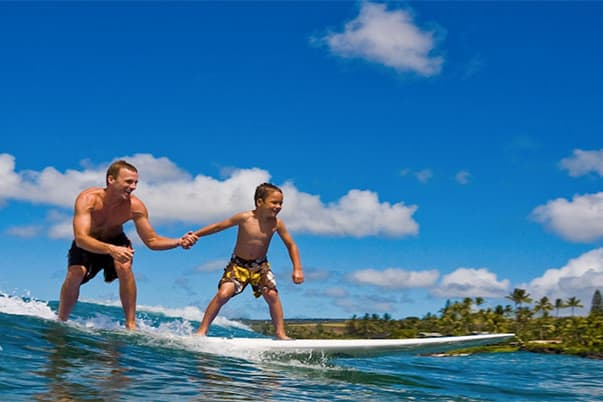 Little kid getting private surf lesson on Kauai